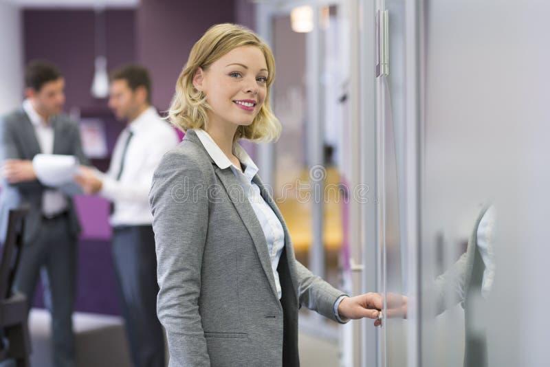 Ładny blond bizneswoman otwiera drzwi w nowożytnym biurze Concep fotografia royalty free