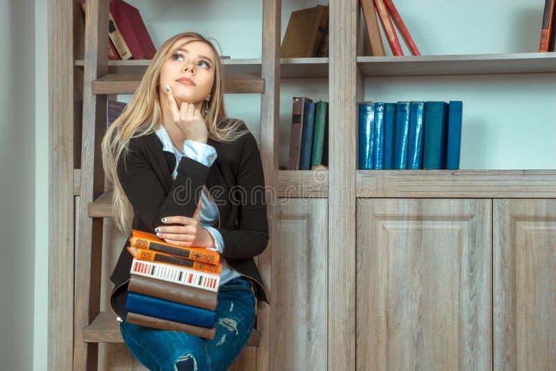 Ładny blond dziewczyny obsiadanie w bibliotece trzyma książki zdjęcia royalty free