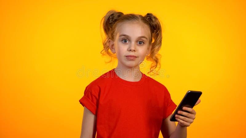 Ładny blond nastoletniej dziewczyny mienia smartphone i patrzeć krzywka, reklama zdjęcie royalty free