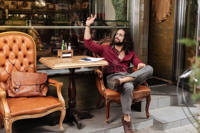 Ładny brunetka mężczyzna dzwoni kelnera obraz royalty free