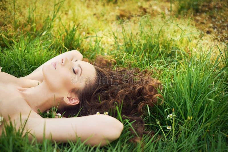 Ładny brunetki kobiety lying on the beach na świeżym gazonie obraz stock