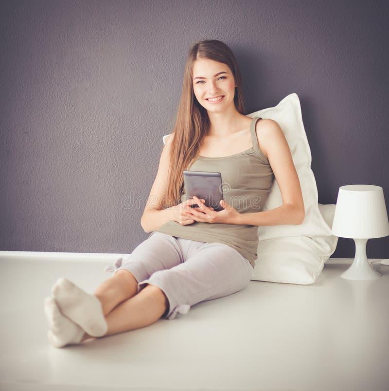 Ładny brunetki kobiety obsiadanie na podłoga z płaskim stołem i poduszką zdjęcia stock