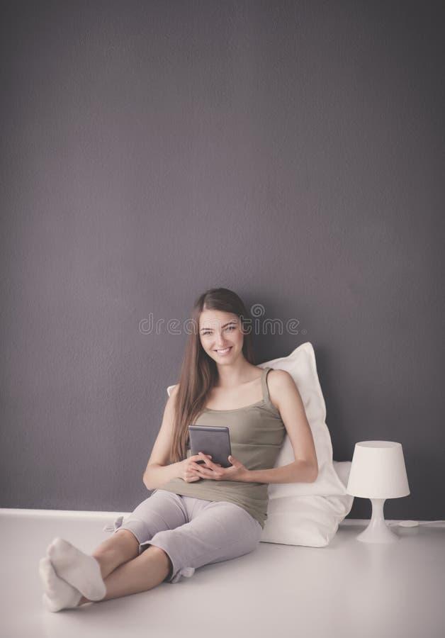Ładny brunetki kobiety obsiadanie na podłoga z płaskim stołem i poduszką fotografia royalty free
