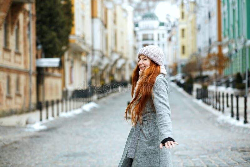 Ładny czerwony z włosami model jest ubranym eleganckiego zima stroju odprowadzenie wewnątrz obrazy stock