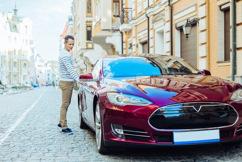Ładny dobry przyglądający mężczyzna trzyma samochodową drzwiową rękojeść obrazy royalty free