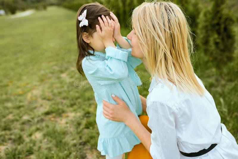 Ładny dzieciak bawić się aport z potomstwami matkuje plenerowego Portret radosna kobieta i jej ?liczny dziecko bawi? si? w parku zdjęcia royalty free