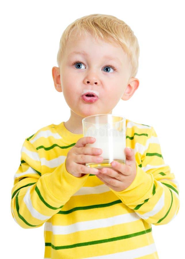 Ładny dzieciak pije mleko od szkła zdjęcia royalty free
