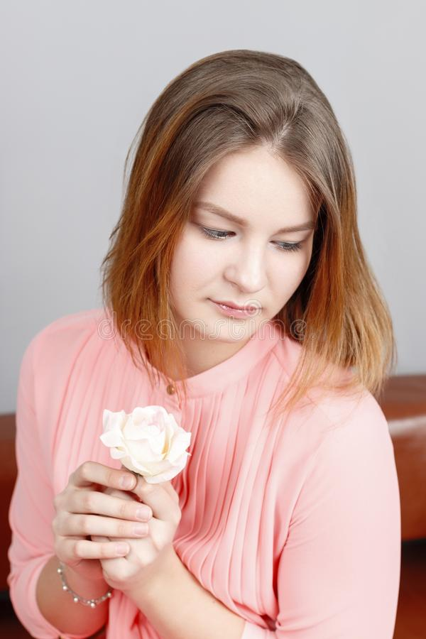 Ładny dziewczyna nastolatek w menchii sukni siedzi z biel różą obraz stock