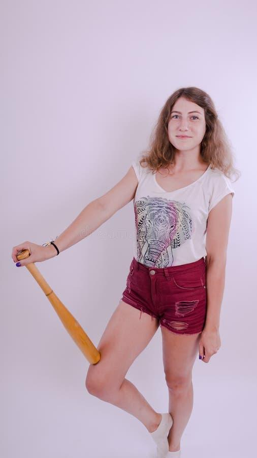 Ładny dziewczyny mienia kij bejsbolowy odizolowywający na bielu obrazy stock