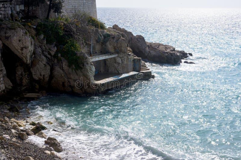 Ładny, Francja, Marzec 2019 Piękny turkusowy morze, góry w mgiełce i bulwar Promenade Des Anglais na ciepłym, obraz royalty free