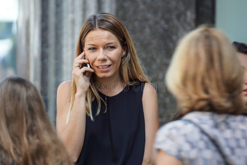 Ładny, Francja 15 2017 Sierpień: Blondynki dziewczyna opowiada na telefonie komórkowym w handlowej ulicy terenie obrazy stock