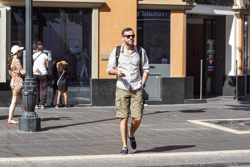 Ładny, Francja 15 2017 Sierpień: Mężczyzna słuchająca muzyka podczas gdy chodzący na ulicie w Ładnym centrum ville zdjęcia stock