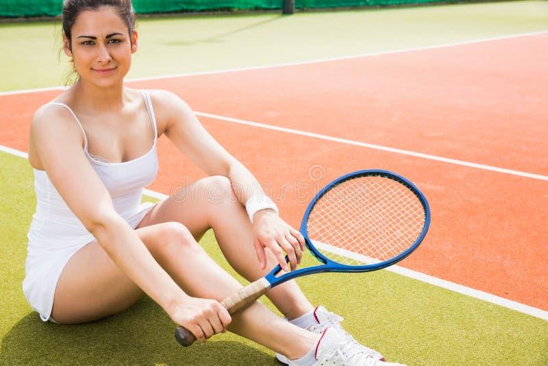 Ładny gracz w tenisa obsiadanie na dworski ono uśmiecha się przy kamerą zdjęcia royalty free