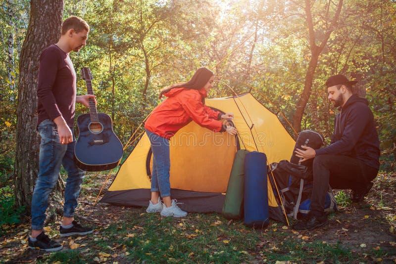 Ładny i pozytywny młodej kobiety przymknięcie wchodzić do namiot Facet na lewicie gitarę w rękach Młody człowiek na dobrze siedzi obrazy royalty free