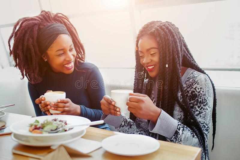 Ładny i pozytywny młody afrykański kobiet śmiać się Siedzą w kawiarni przy stołem Modele filiżanki z kawą w rękach one obrazy royalty free