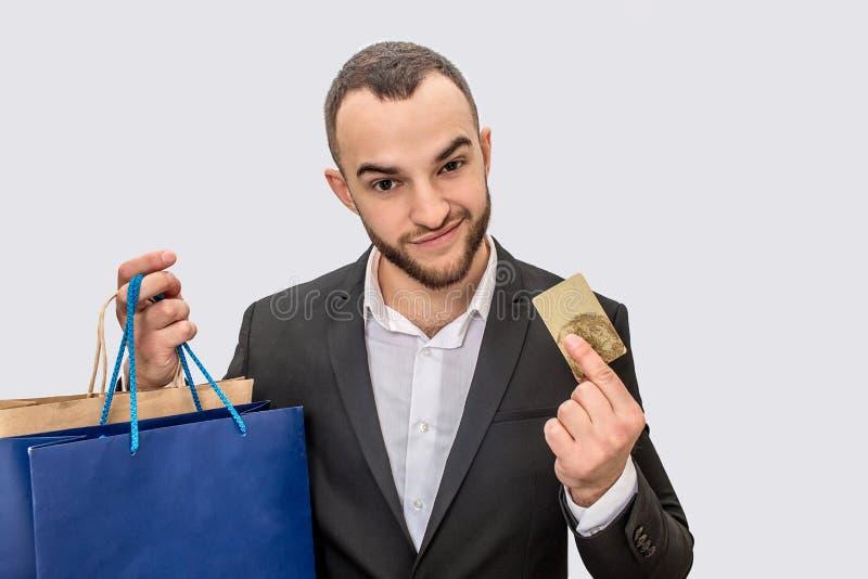 Ładny i ufny młody człowiek w kostiumu stoi kartę kredytową i pokazuje Patrzeje prosto Młody człowiek torby na zakupy wewnątrz zdjęcie stock