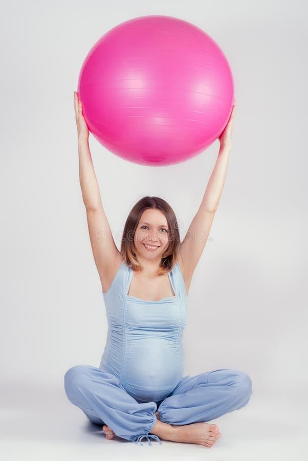 Ładny kobieta w ciąży robi ćwiczeniu z dużą gimnastyczną piłką zdjęcia royalty free