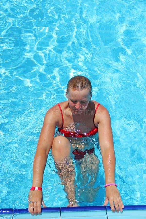 Ładny kobiety narządzanie pływać w basenie podczas wakacje fotografia stock