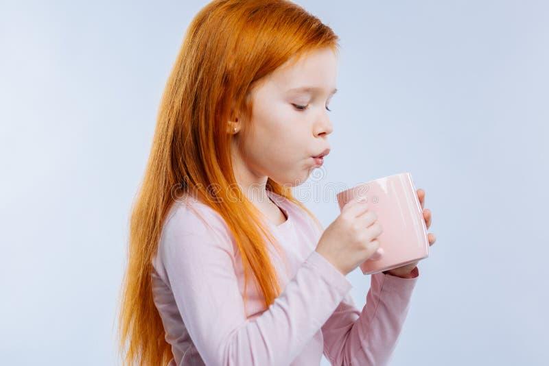 Ładny młodej dziewczyny dmuchanie przy filiżanką herbata zdjęcie stock