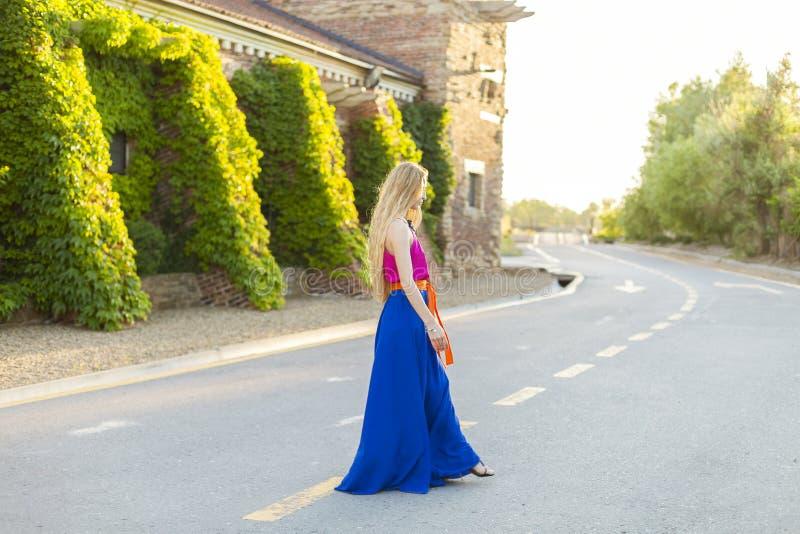 Ładny młodej kobiety odprowadzenie na ulicie w długiej sukni zdjęcia stock