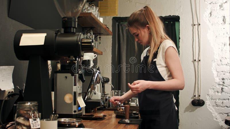 Ładny młody żeński barista waży kawę groszkuje na skala przed warzyć filiżankę kawy zdjęcia stock