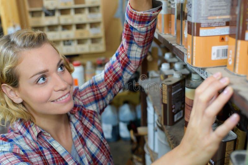 Ładny młody żeński cieśla wybiera lakier w woodshop fotografia stock