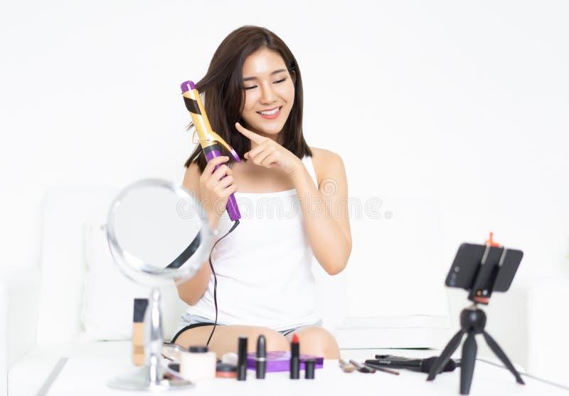 Piękna, młoda azjatycka blogerka używająca prostowania włosów z h obraz royalty free