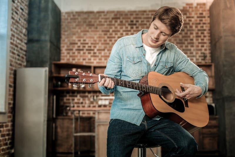 Ładny młody człowiek bawić się gitarę obrazy royalty free