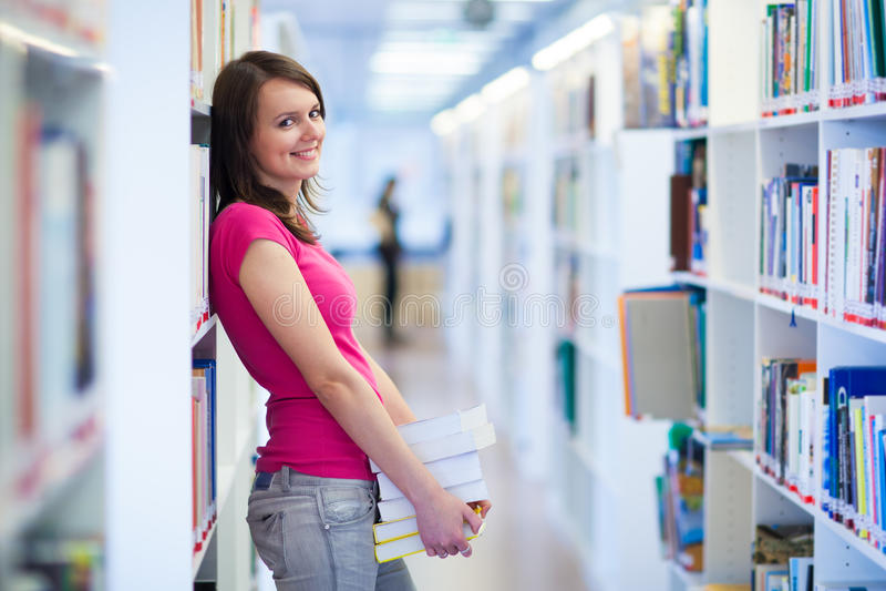 Ładny młody student collegu w bibliotece obraz royalty free