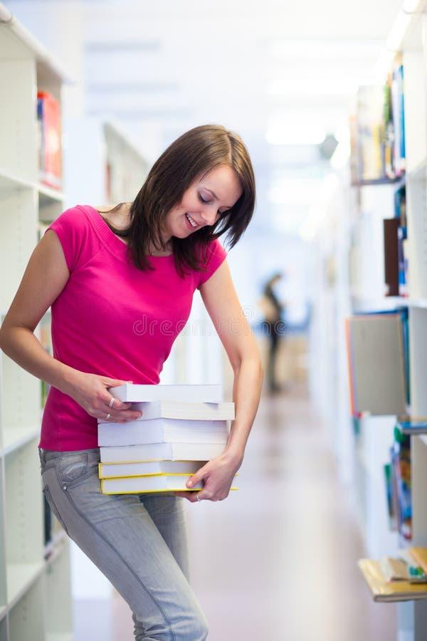 Ładny młody student collegu w bibliotece zdjęcia stock