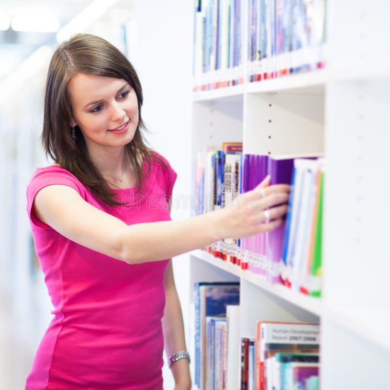 Ładny młody student collegu w bibliotece obraz stock