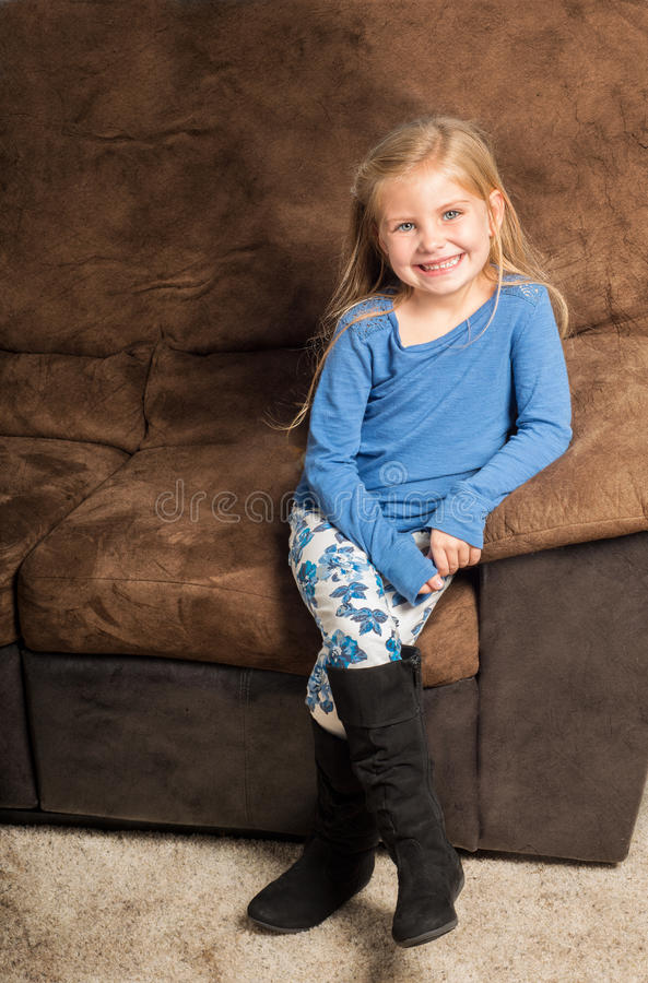 Ładny małej dziewczynki obsiadanie na kanapie z dużym uśmiechem fotografia royalty free