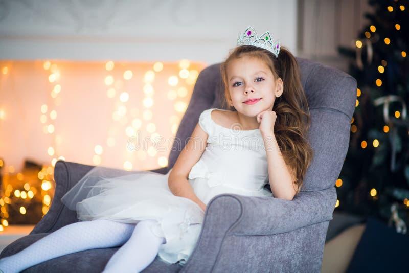 Ładny małej dziewczynki obsiadanie w karle Magiczna i świąteczna atmosfera obrazy stock