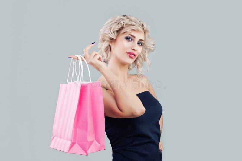 Ładny model z torbami na zakupy Piękna kobieta z krótkim kędzierzawym włosy i makeup fotografia royalty free