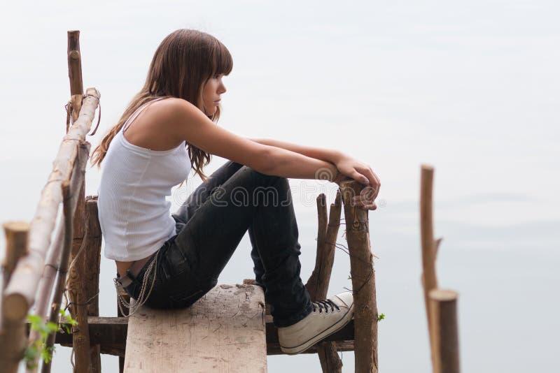 Ładny nastoletniej dziewczyny obsiadanie na doku obok rzeki na kawalerze obraz stock