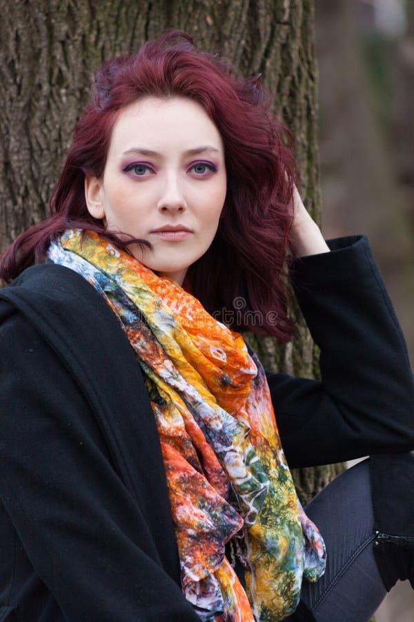 Ładny niebieskie oko kobiety zimy portret plenerowy w parku przeciw drzewnemu czarnemu żakietowi i kolorowemu szalikowi zdjęcia royalty free