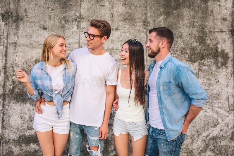 Ładny obrazek blondynki dziewczyny pozycja z jej przyjaciółmi na popielatym backgroubnd i patrzeć one Jest uśmiechnięta Chłopiec  fotografia royalty free