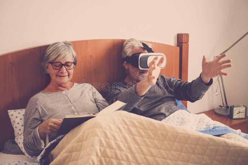 Ładny piękny pary caucasian dorośleć mężczyzny i kobiety w sypialnia pobycie na łóżku w domu podczas ranku czyta papier obraz stock