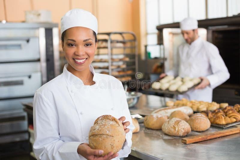 Ładny piekarniany ono uśmiecha się przy kamerą z bochenkiem obraz stock