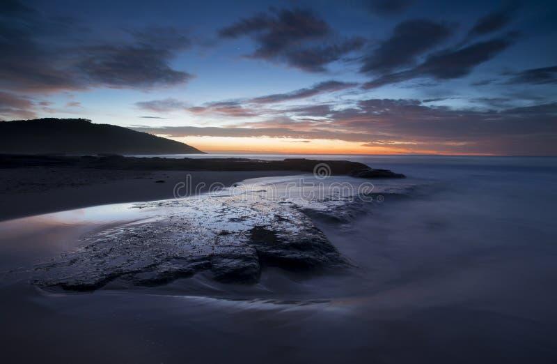 Ładny plażowy wschód słońca nad skałami fotografia royalty free