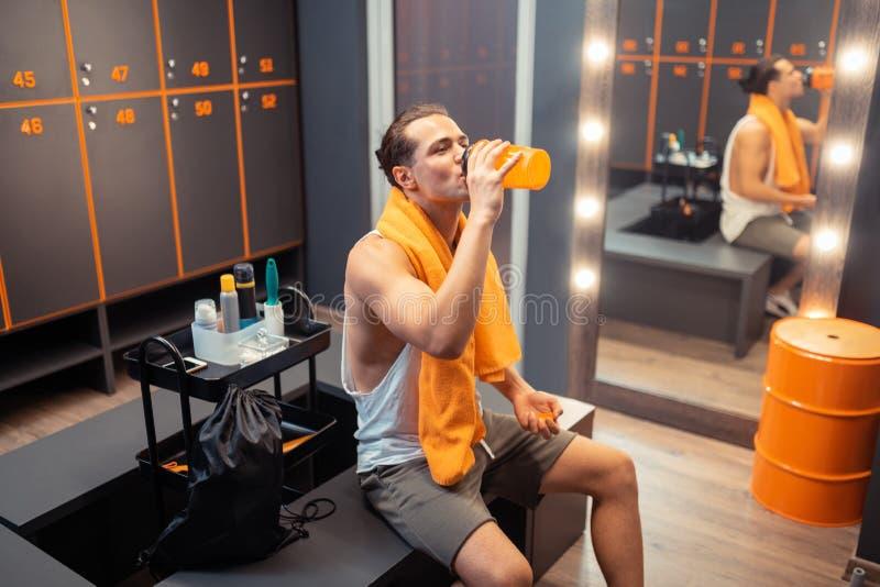Ładny pozytywny mężczyzna pije świeżą wodę od butelki obrazy stock