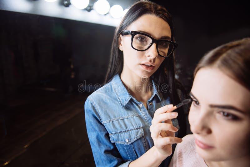 Ładny sprawny makeup artysta trzyma oka muśnięcie zdjęcia royalty free