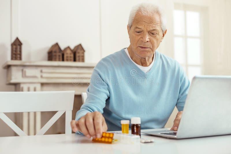 Ładny starsza osoba mężczyzna obsiadanie przed laptopem zdjęcie royalty free
