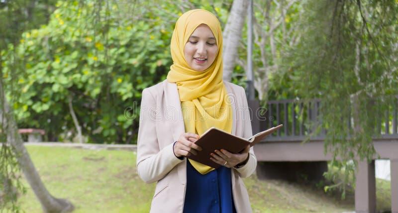 Ładny student collegu cieszy się czytanie w parku fotografia royalty free