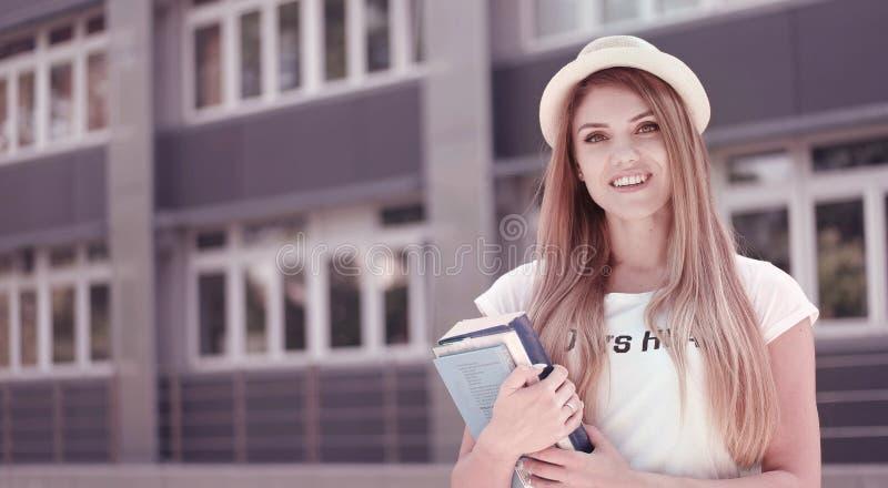 Ładny uczeń z książkami Przeciw uniwersytetowi obraz stock