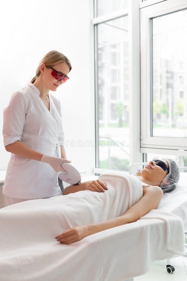Ładny wykwalifikowany dermatolog jest ubranym specjalnych ochronnych szkła fotografia royalty free