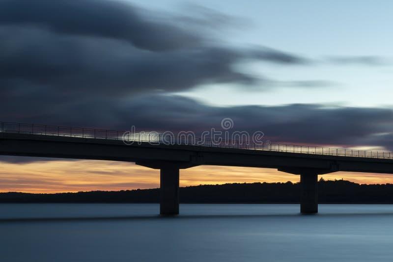 Ładny zmierzch po wiaduktu krzyżuje nad jeziorem obraz royalty free