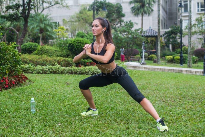 Ładnych potomstw dysponowana kobieta robi rozciąganiu ćwiczy w parku Sprawności fizycznych boczni lunges outdoors obrazy royalty free