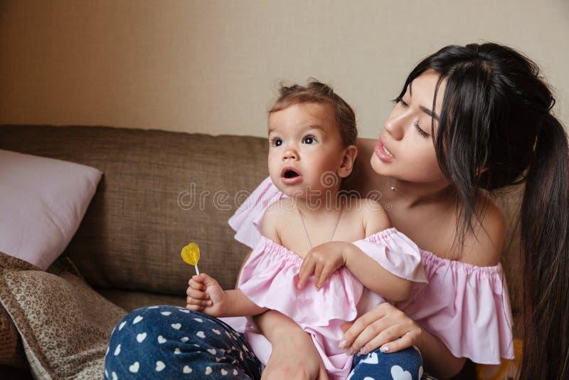 Ładnych potomstw macierzysty obsiadanie na kanapie z małą szokującą córką zdjęcia stock