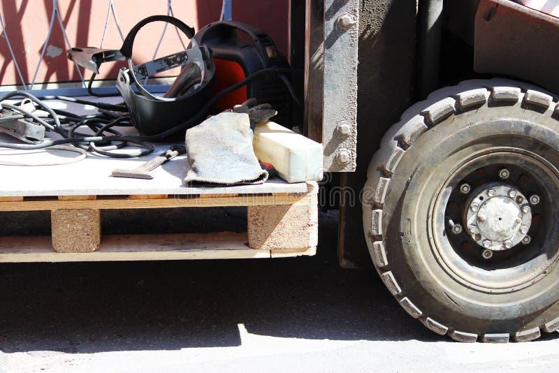 Ładowacz trzyma drewnianego barłóg z spawalniczym wyposażeniem dla załatwiać metali grilles okno zdjęcia stock